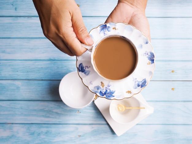 A vista superior da mão com café quente na caneca cerâmica com copo de chá ajustou-se na tabela de madeira.