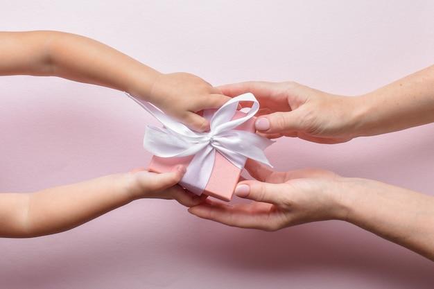 A vista superior da mão de uma criança e da mão de uma mulher passa por uma caixa de presente rosa com uma fita branca em um fundo rosa. feliz aniversário, feliz dia das mães.
