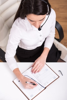 A vista superior da mulher atrativa está trabalhando em um centro de chamadas.