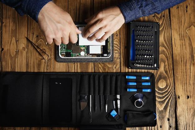 A vista superior das mãos funciona em um dispositivo eletrônico quebrado para consertá-lo perto da bolsa de ferramentas e na mesa de madeira na loja de serviços