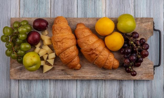 A vista superior de croissants com uvas pluota nectacotes e queijo na tábua de cortar no fundo de madeira