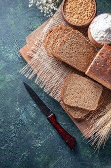 A vista superior de fatias de pão preto, farinha de trigo na toalha de cor nude, espiga a flor em tábuas de corte em fundo de cores mistas