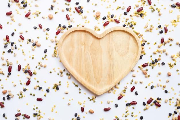 A vista superior de leguminosa diferentes com coração de madeira vazio deu forma à placa isolada no fundo branco.