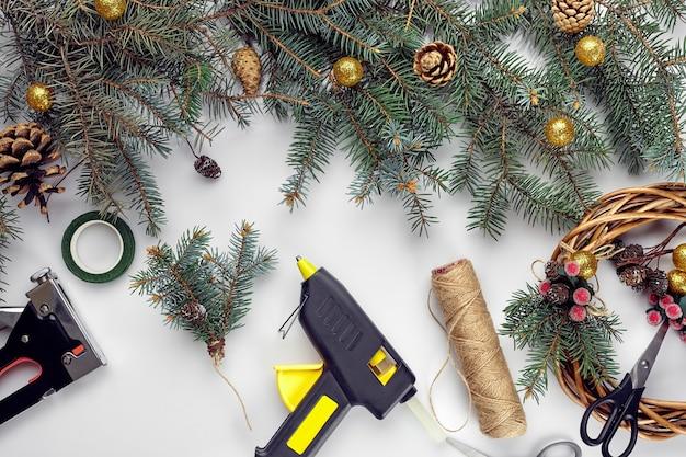 A vista superior de mãos femininas faz uma guirlanda de natal embalada em presentes e pergaminhos de ramos de abeto e ferramentas ...