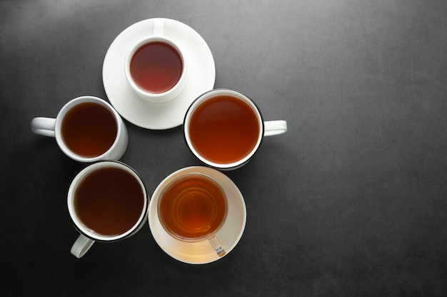 A vista superior de muitos copos, canecas com chá quente bebe na obscuridade, copyspace. hora do chá ou freio de chá. bebida de outono. imagem enfraquecida com xícaras de chá.