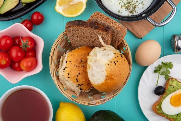 A vista superior de pães no balde com tomate limão ovo ovo frito na panela na placa de madeira da cozinha em azul
