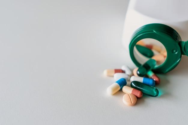 A vista superior de tabuletas da medicina derrama do frasco de comprimidos do fundo de mármore da textura branca. estilo de vida médico de cuidados de saúde.