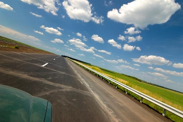 A vista superior de um carro é uma estrada lisa cercada pela bela natureza de verão com campos de árvores verdes e céu azul em um dia quente e ensolarado de verão