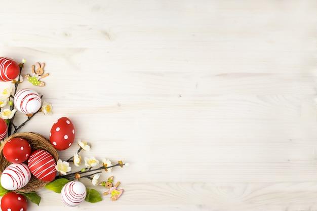 A vista superior de um eeaster colorido eggs no ninho e na mola floresce em um fundo de madeira claro com espaço de mensagem.