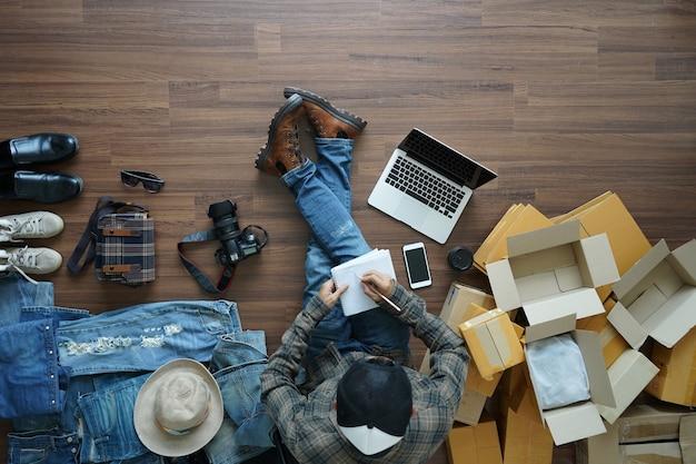 A vista superior de um homem escrevendo em um caderno é freelancer com seu negócio particular em casa