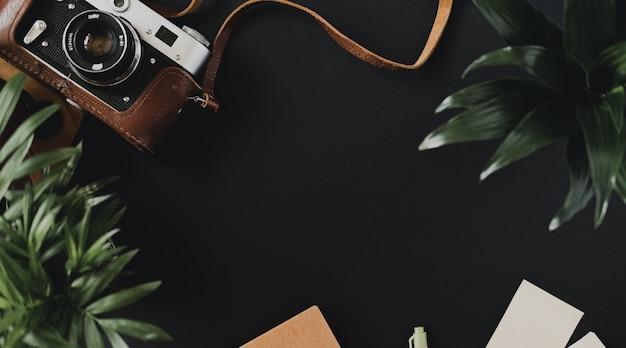 A vista superior de uma câmera de filme plana em uma caixa encontra-se em uma mesa preta ao lado de cadernos e uma caneta. conceito de espaço de trabalho do artista ou fotógrafo. espaço de publicidade