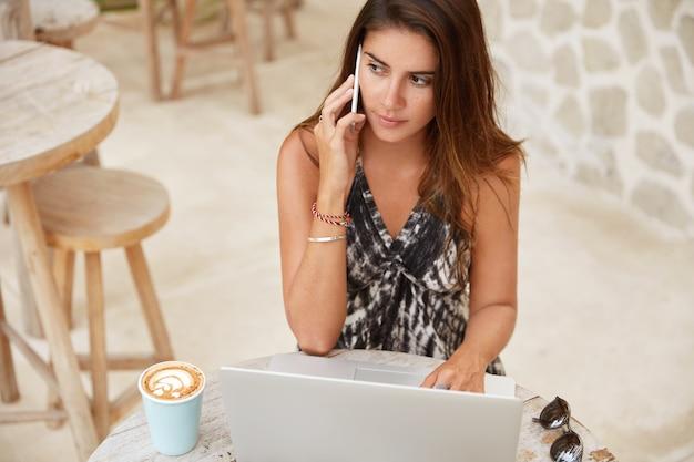 A vista superior de uma mulher atraente pensativa tem uma expressão atenciosa enquanto fala por telefone inteligente com um parceiro de negócios, trabalha remotamente em um laptop, aprecia um cappuccino aromático em uma cafeteria