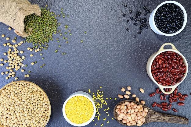 A vista superior de várias nozes mistas inclui: feijão, soja, feijão mungo, vigna mungo ou grama preta, amendoim, moong dal, na mesa preta.