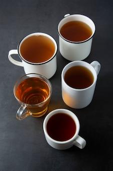 A vista superior de vários copos, canecas com chá quente bebe na obscuridade, copyspace. hora do chá ou freio de chá. bebida de outono. imagem enfraquecida com xícaras de chá.