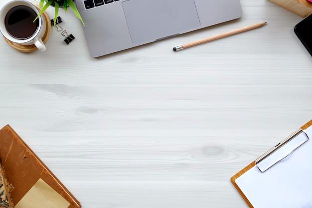 A vista superior disparou das mãos do espaço de trabalho e do homem usando o smartphone na mesa de escritório branca.
