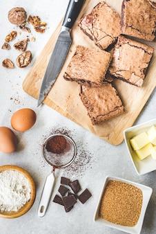 A vista superior do bolo caseiro recém-assado da brownie arranjou com os ingredientes da receita em rústico branco.