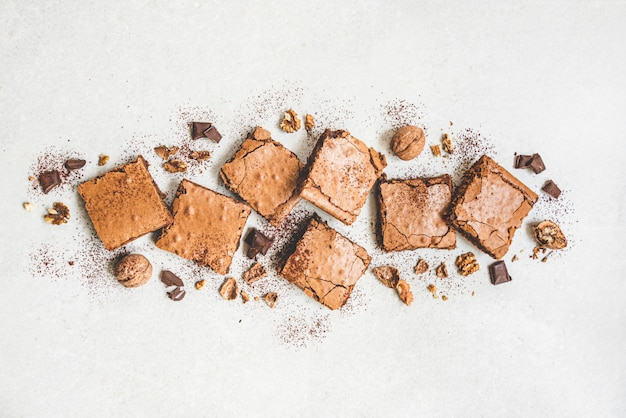 A vista superior do bolo caseiro recentemente cozido da brownie cortou nos quadrados em rústico branco.