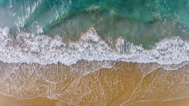 A vista superior do céu da onda do mar e a areia encalham a paisagem.