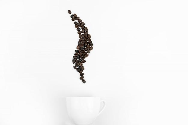 A vista superior do copo branco com grãos de café em forma de vapor no blackground branco.
