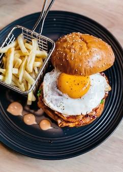 A vista superior do hamburguer saboroso com ovo frito serviu com as fritadas na placa preta na tabela de madeira.