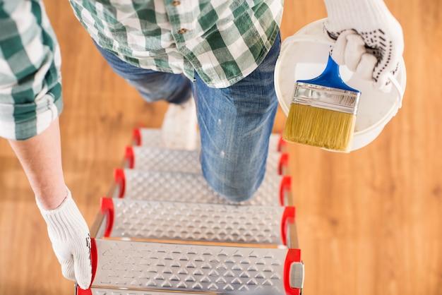 A vista superior do homem está estando em uma escada com uma escova de pintura.