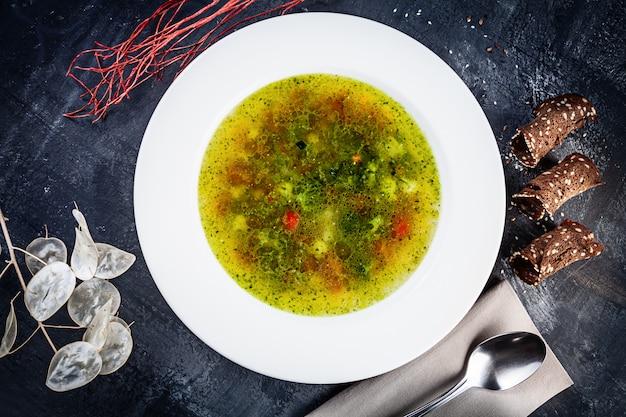 A vista superior do minestrone serviu na bacia branca no fundo escuro. sopa de origem italiana feita com legumes. alimentação saudável para o almoço. conceito de comida vegetariana deliciosa