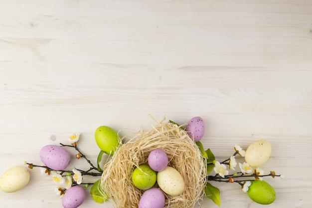 A vista superior do ovos da páscoa coloridos no ninho e na mola floresce em um fundo de madeira claro com espaço de mensagem.