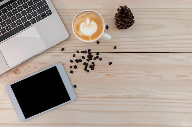 A vista superior do tablet está no caderno, com uma caneta, um caderno e um café com leite em uma mesa de madeira.