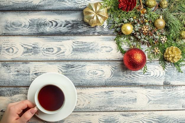 A vista superior enfeita uma xícara de galhos de árvore de abeto chá em uma superfície de madeira