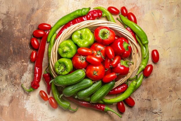 A vista superior forma um círculo com pimenta e tomate cereja, uma cesta de legumes em um círculo no fundo âmbar