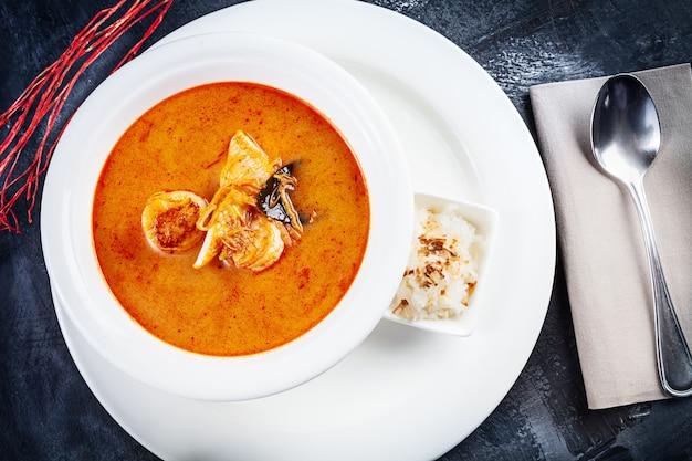 A vista superior na sopa de tom yum serviu no prato branco com arroz. sopa com camarão, frutos do mar, leite de coco e pimenta no espaço da cópia da tigela. cozinha tradicional da tailândia. almoço comida com espaço de cópia