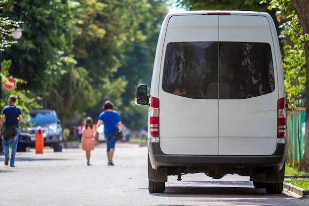 A vista traseira da van de microônibus de luxo comercial de tamanho médio branco de passageiros estacionou na sombra da árvore verde na rua i da cidade de verão com silhuetas borradas de pedestres e carros sob árvores verdes.
