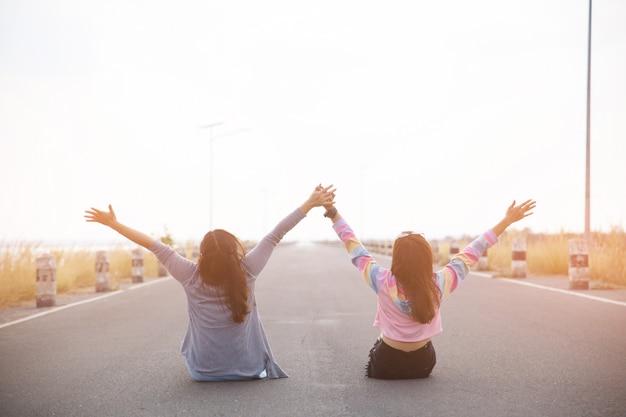 A vista traseira de dois jovem sentado na estrada, olhando para longe e mãos para cima.