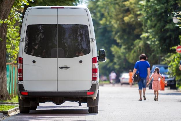 A vista traseira do passageiro branco tamanho médio van comercial de microônibus de luxo estacionou na rua da cidade de verão.