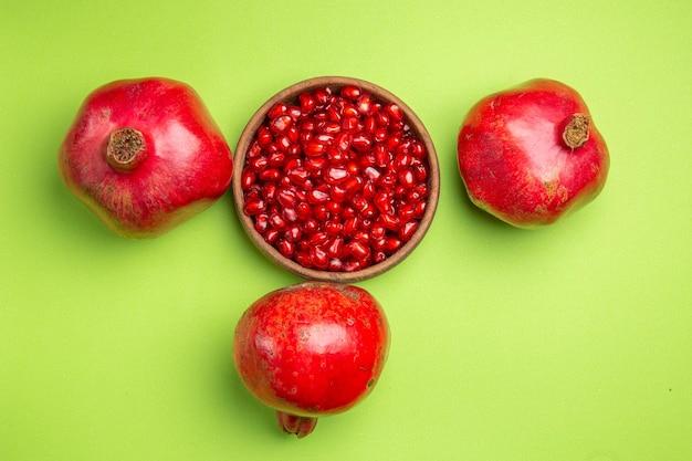 A visualização em close-up de cima frutifica as apetitosas maçãs e as sementes de romã na superfície verde