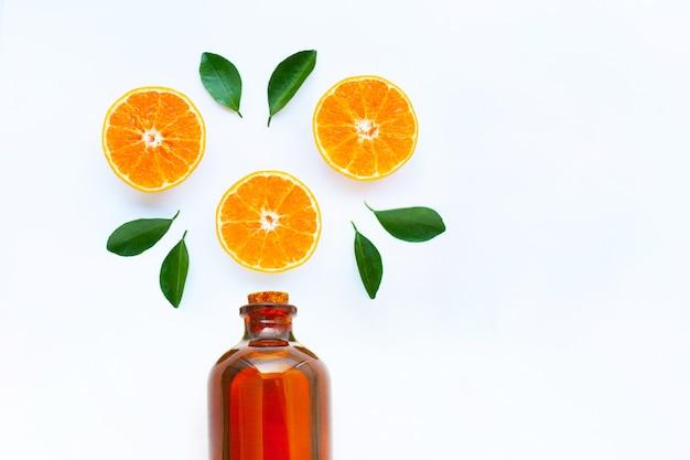 A vitamina alta c, laranja frutifica com a garrafa de óleo essencial no fundo branco.
