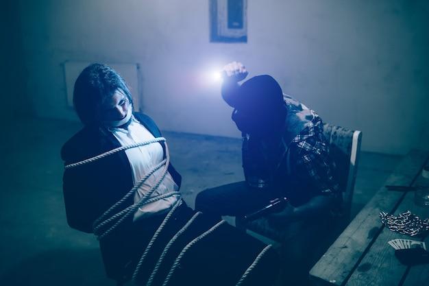 A vítima está sentada na cadeira. seu corpo está amarrado. ele não consegue olhar para seu sequestrador por causa da luz que vem da pequena lâmpada na testa do assassino. o homem mascarado está sentado na frente de sua vítima.