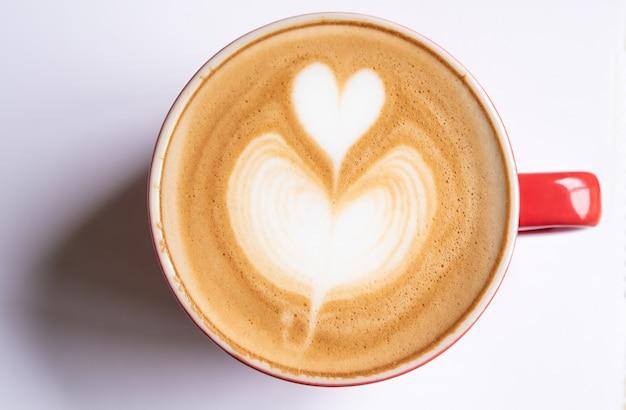 A xícara de café com uma bolha dada forma coração descansa em um fundo branco.