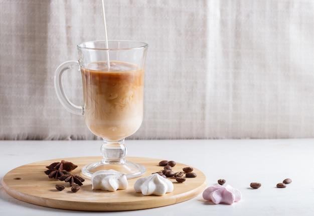 A xícara de café de vidro com creme derramou sobre e merengues em uma placa de madeira em um fundo branco.