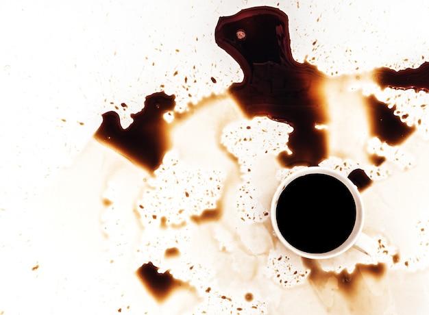 A xícara de café derramou no fundo branco, vista superior. para design de propaganda grunge, copie o espaço