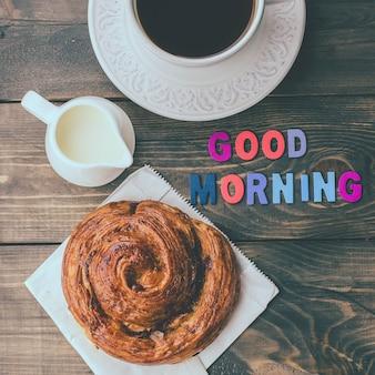A xícara de café e a madeira rotulam o bom dia no fundo de madeira da tabela. vista de cima, copie o espaço