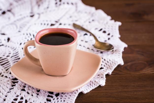 A xícara de café é guardanapo de malha openwork na mesa de madeira