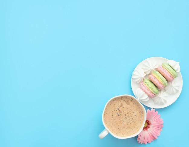 A xícara de cappuccino e deliciosos macarons com merengues brancos em um prato branco
