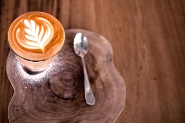 A xícara de cappucino quente está no fundo da mesa de madeira. é latte art no topo
