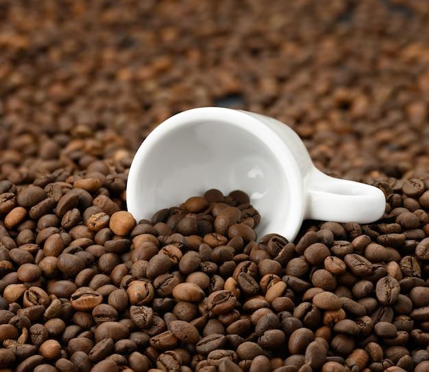 A xícara de cerâmica branca repousa sobre uma pilha de grãos de café arábica torrados e robusta, full frame