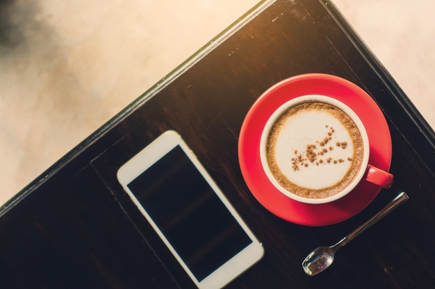 A xícara de cerâmica de café cappuccino quente na mesa de madeira no restaurante