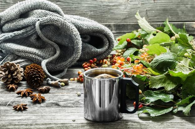 A xícara de chá em um fundo bonito de madeira com blusa de inverno, frutas, outono