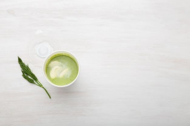 A xícara de sopa verde com pedaços de legumes está sobre uma mesa branca com ervilhas verdes. alimentação saudável