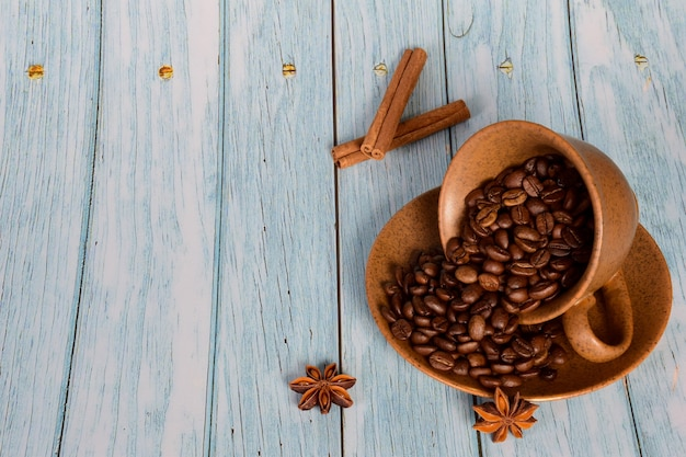 A xícara está deitada de lado em um pires com grãos de café dentro. ao lado dele encontra-se anis e canela em um fundo de madeira. há um lugar à esquerda para uma inscrição
