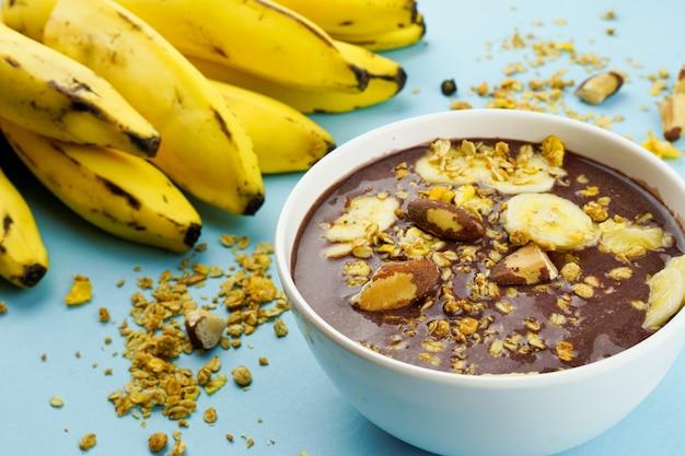 Aai brasileiro em uma tigela branca com granola de banana e castanhas vista superior